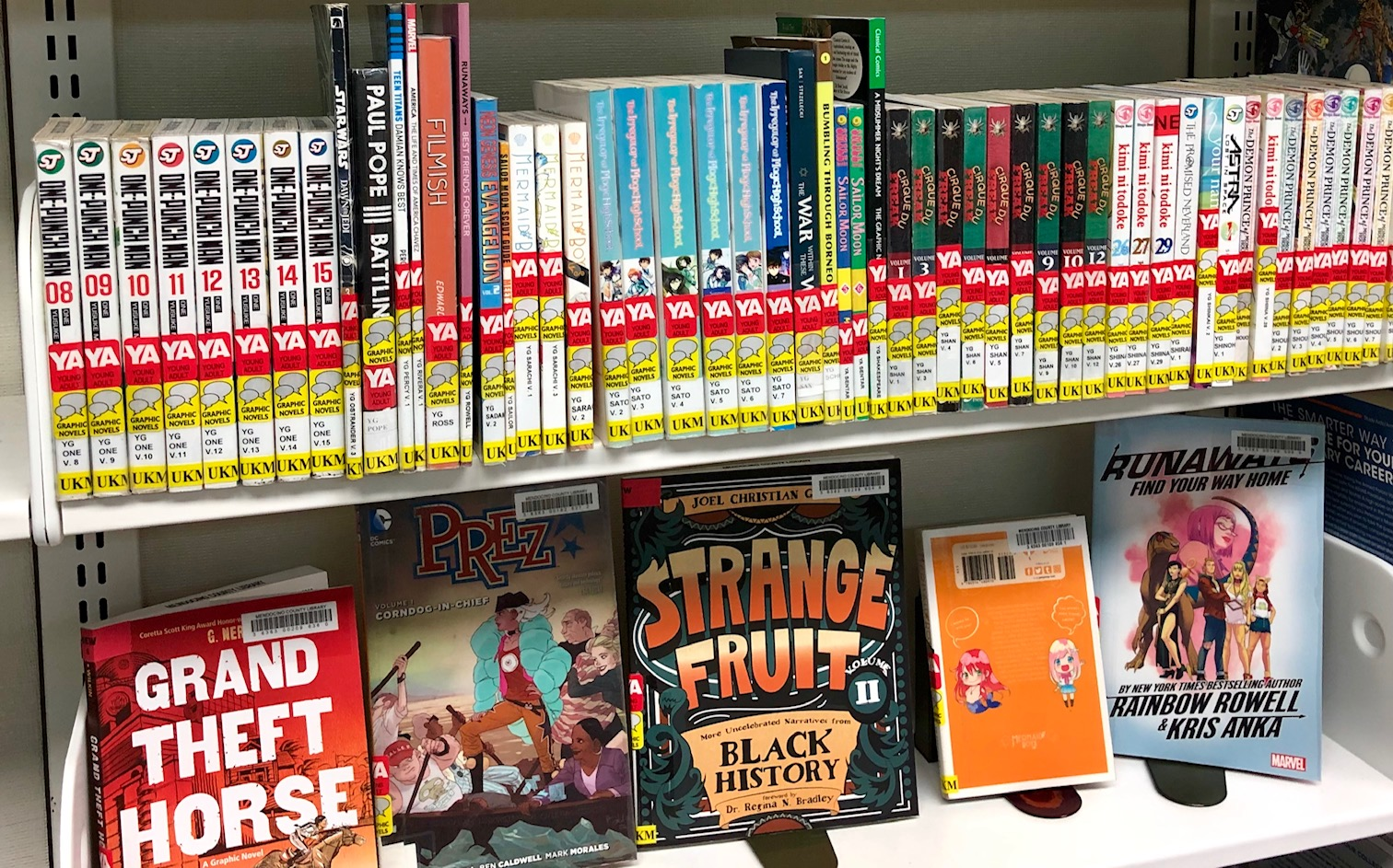 two shelves of manga books for teens, some with spines facing out and some with covers facing out.