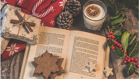 open book with star cookie, present and glass of milk