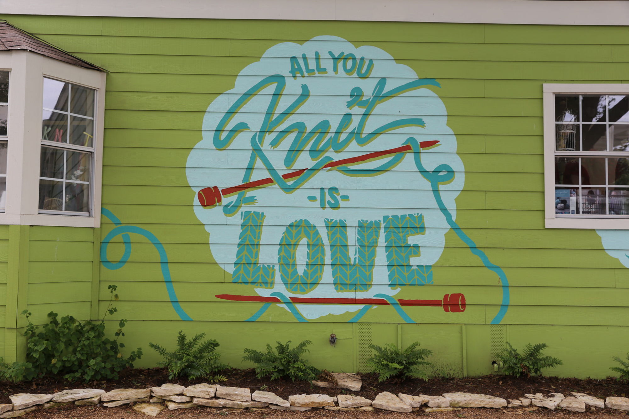 """All you knit is love"" sign on wall of building"