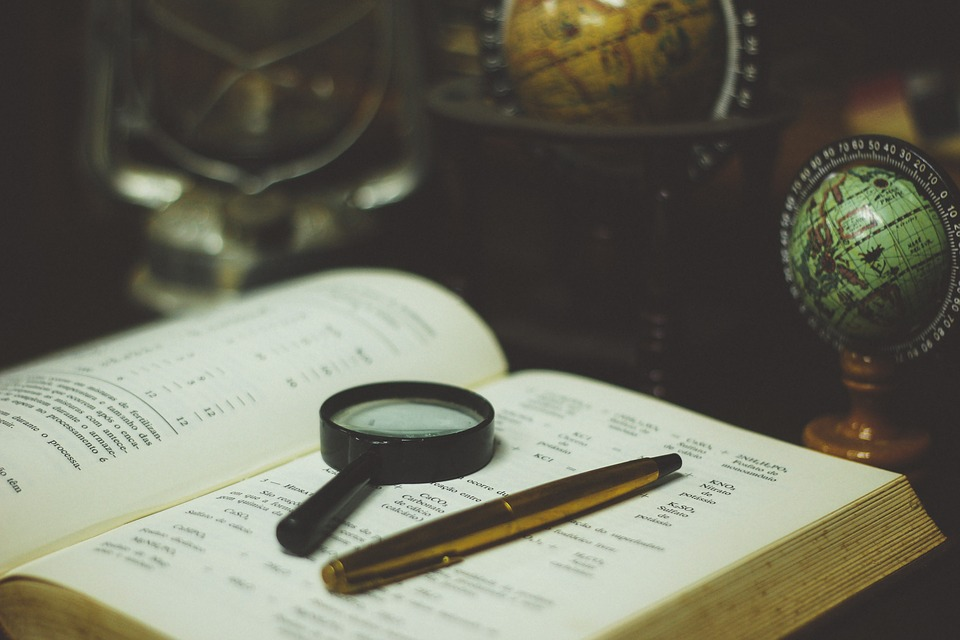 Magnifying glass and pen resting on book